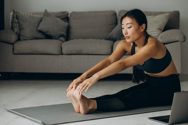 Vrouw die zich thuis uitstrekt op yogamat