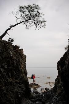 Vrouw die zich tussen de rotsen op de kustlijn op het overzees met wandelingsrugzak bevindt