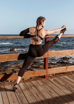Vrouw die zich uitstrekt aan het strand