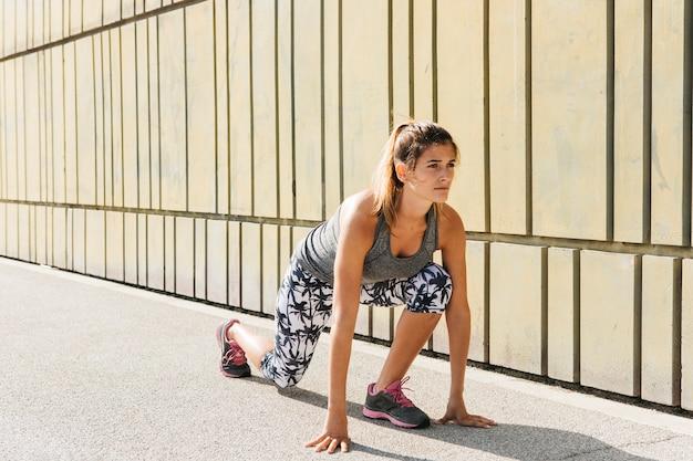 Vrouw die zich uitstrekt buitenshuis voor hardlopen