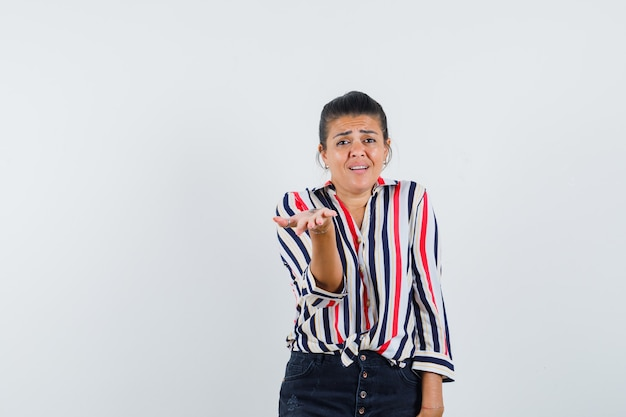 Vrouw die zich uitstrekt hand in verbaasd gebaar in shirt, rok
