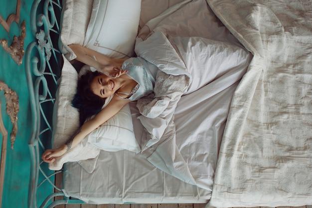 Vrouw die zich uitstrekt in bed na wakker worden