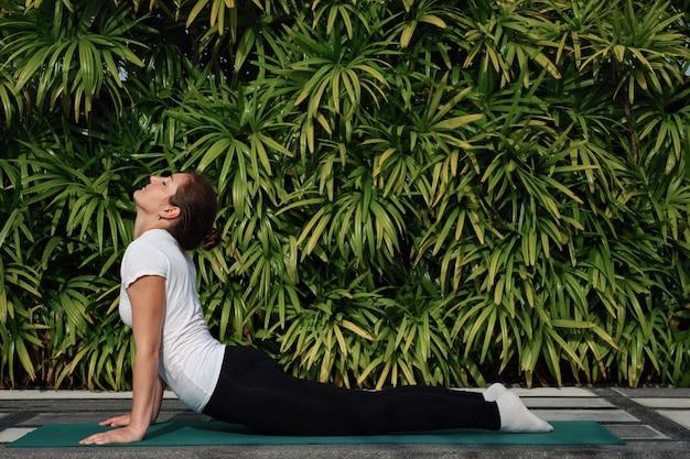 Vrouw die zich uitstrekt op een achtergrond van groen gebladerte. yoga buitenshuis.