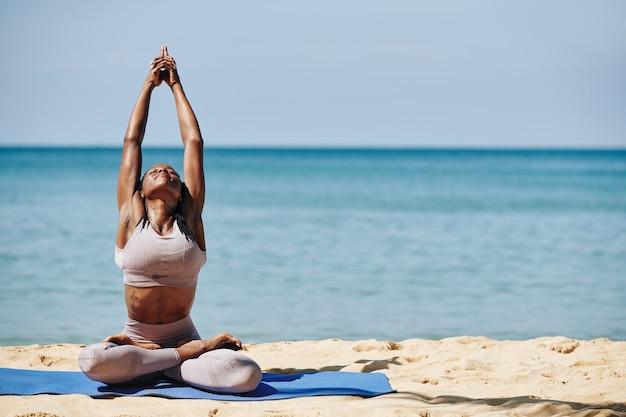 Vrouw die zich uitstrekt op het strand
