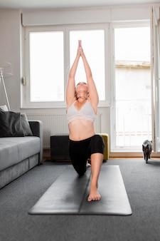 Vrouw die zich uitstrekt op yoga mat