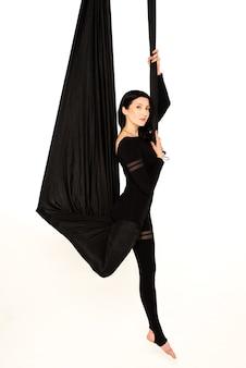 Vrouw die zich uitstrekt op zwarte hangmat.