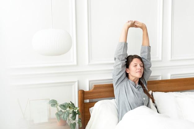 Vrouw die zich uitstrekt terwijl ze wakker wordt in haar bed