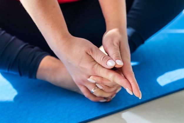 Vrouw die zich uitstrekt tijdens yoga-oefening voor gezondheid en revalidatie terug. gezondheidszorg