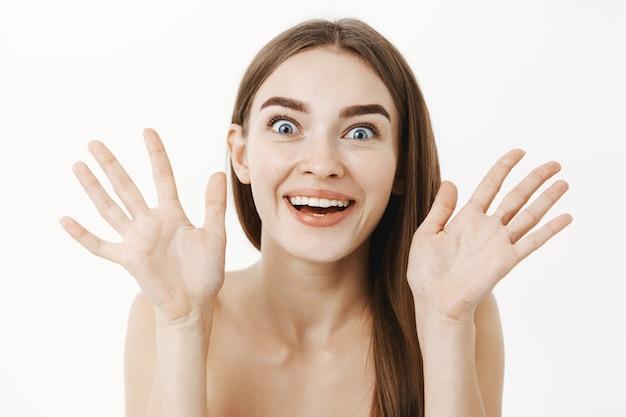 Vrouw die zich verrukt voelt met het positieve resultaat van de huidverzorgingsprocedure die de handpalmen in de buurt van het gezicht houdt, breed glimlachend en starend met verbazing en verbazing