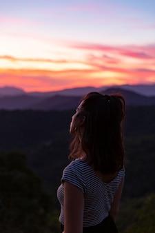 Vrouw die zich vooraan op een mooie achtergrond bij dageraad bevindt