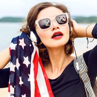 Vrouw die zich voordeed op het strand luisteren muziek in haar stijlvolle grote koptelefoon close-up