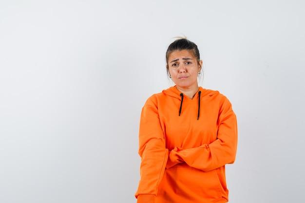 Vrouw die zich voordeed terwijl ze in een oranje hoodie stond en er van streek uitzag