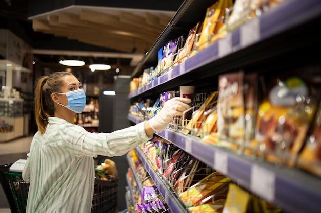 Vrouw die zichzelf beschermt tegen het coronavirus tijdens het winkelen in de supermarkt