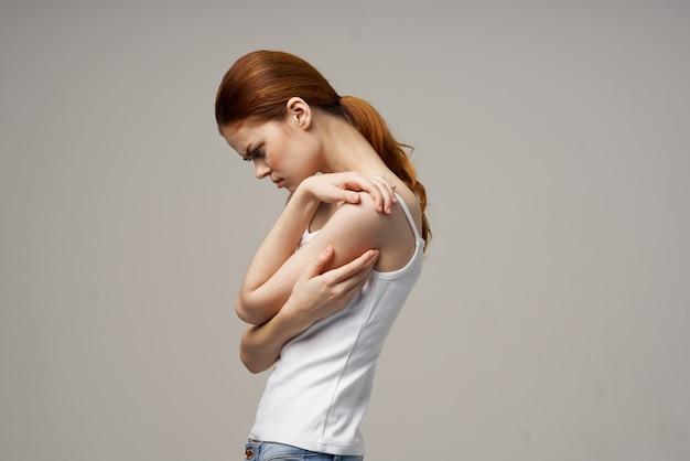 Vrouw die zichzelf bij de schouders op beige achtergrond bijgesneden weergave