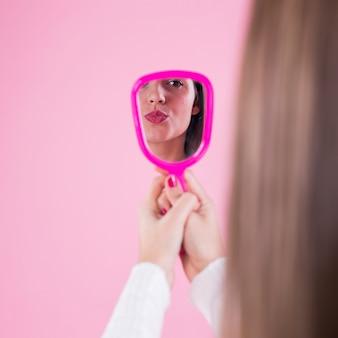 Vrouw die zichzelf in spiegel en blazende kus bekijkt