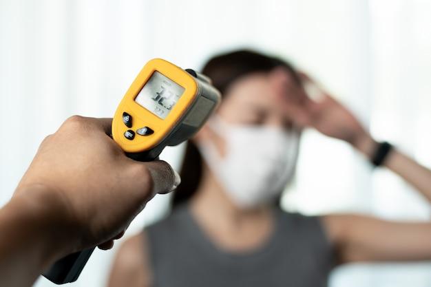 Vrouw die ziek voelt dragend beschermend masker. met de handcontrole van de beveiliging bij poorten gebruikt u een digitale thermometer die de temperatuur controleert.