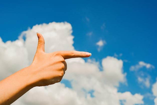 Vrouw die zijn hand en wolkenhemel richt