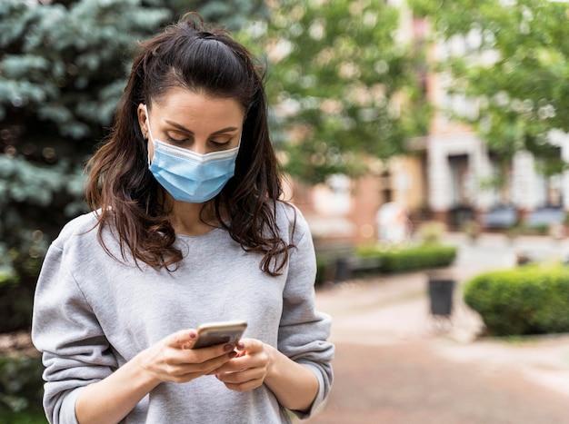 Vrouw die zijn telefoon controleert terwijl het dragen van een gezichtsmasker met exemplaarruimte