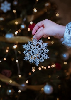 Vrouw die zilveren sneeuwvlok in hand houdt