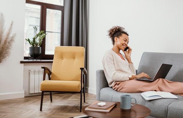 Vrouw die zittend op de bank werkt