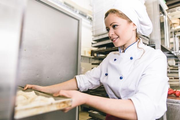 Vrouw die zoete croissants in de patisserie voorbereiden