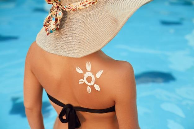 Vrouw die zonnebrandcrème op gebruinde schouder toepast
