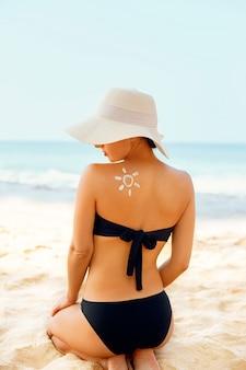 Vrouw die zonnebrandcrème toepast op de gebruinde schouder in de vorm van de zon.
