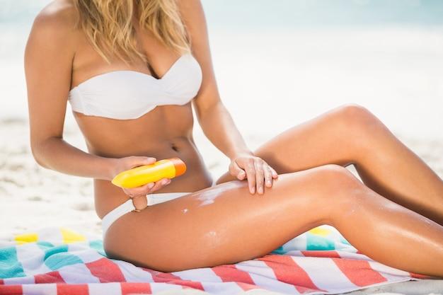 Vrouw die zonnebrandcrème toepast