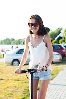Vrouw die zonnebril draagt die een autoped berijden