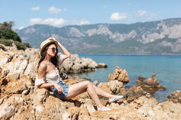 Vrouw die zonnebril draagt die zich op rotsen bevindt