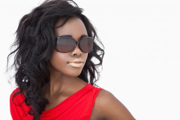 Vrouw die zonnebril en een rode kleding draagt