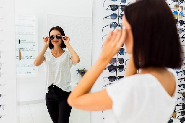 Vrouw die zonnebril in spiegel controleert