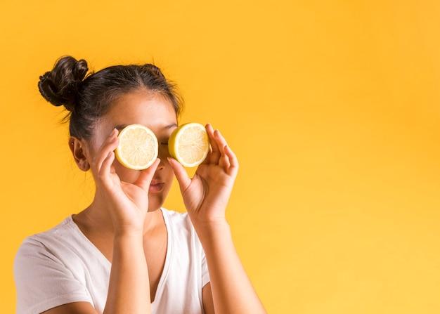 Vrouw die zonnebril van de helften van citroen maakt