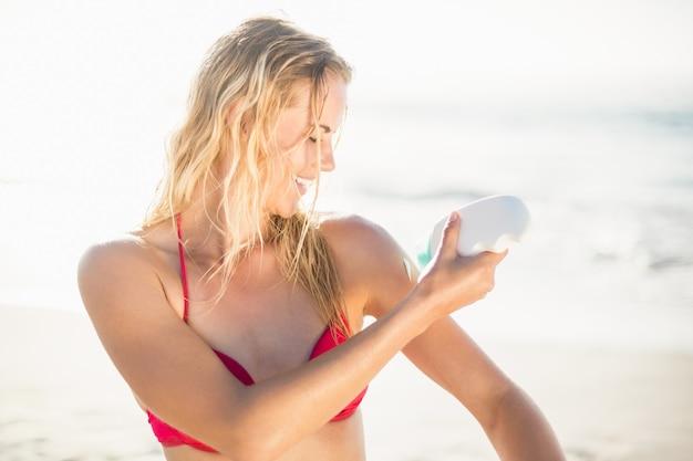 Vrouw die zonneschermlotion op het strand toepast