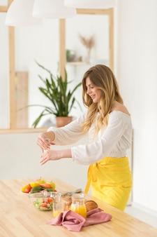 Vrouw die zout in salade zijaanzicht zet