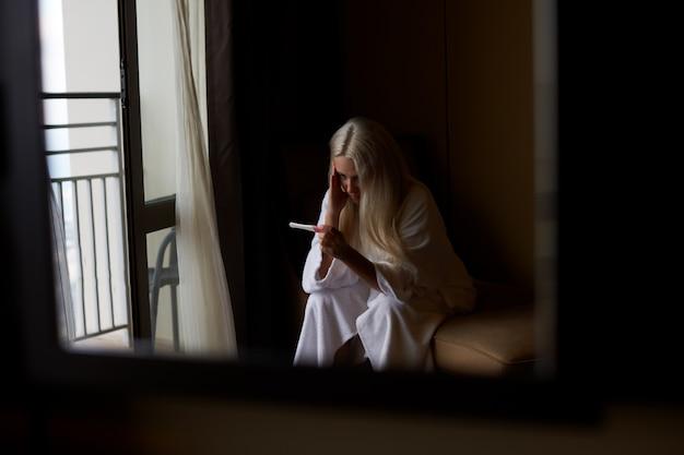 Vrouw die zwangerschapstest bekijkt. zijaanzicht