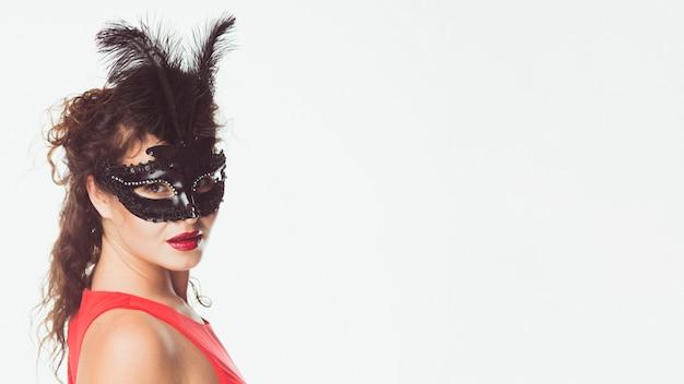 Vrouw die zwart masker met veren draagt