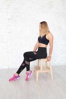 Vrouw die zwarte beenkappen en hoogste zitting op stoel draagt