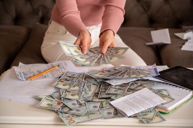 Vrouw die zwarte glazen draagt die geld tonen