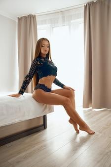 Vrouw die zwarte kanten kleren draagt die op bed stellen