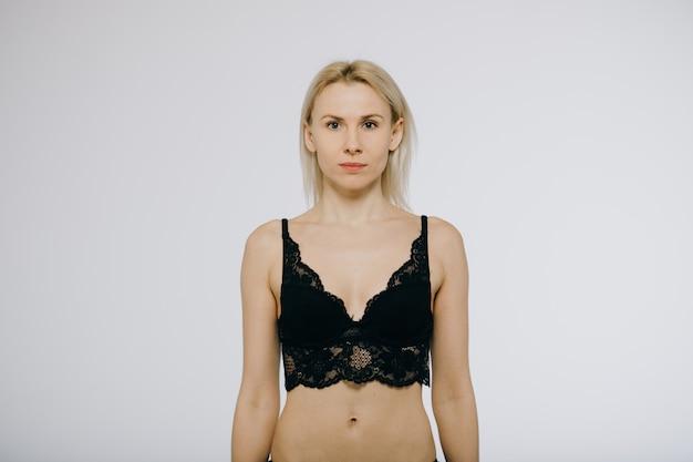 Vrouw die zwarte lingerie uit één stuk draagt die op wit wordt geïsoleerd
