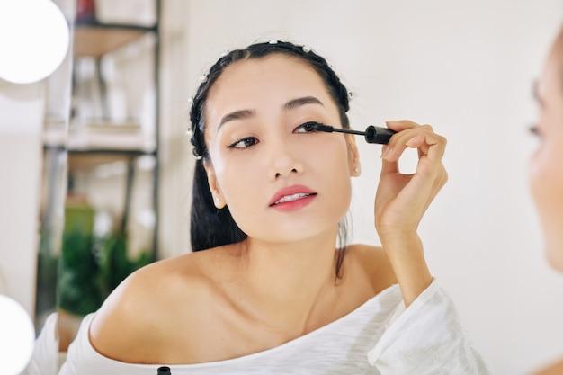 Vrouw die zwarte mascara toepast