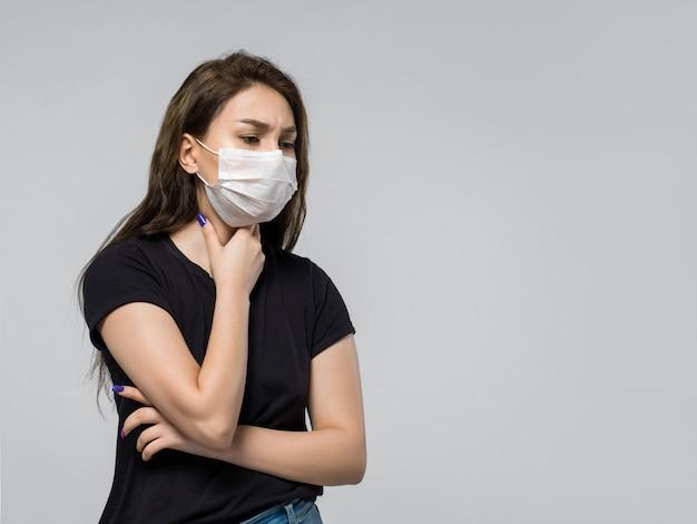 Vrouw die zwarte t-shirt en medisch beschermend masker draagt dat ziek voelt