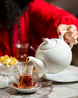 Vrouw die zwarte thee van theepot gieten in armudu-glas