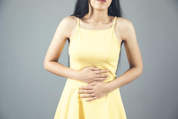 Vrouw dient buikpijn op grijs in