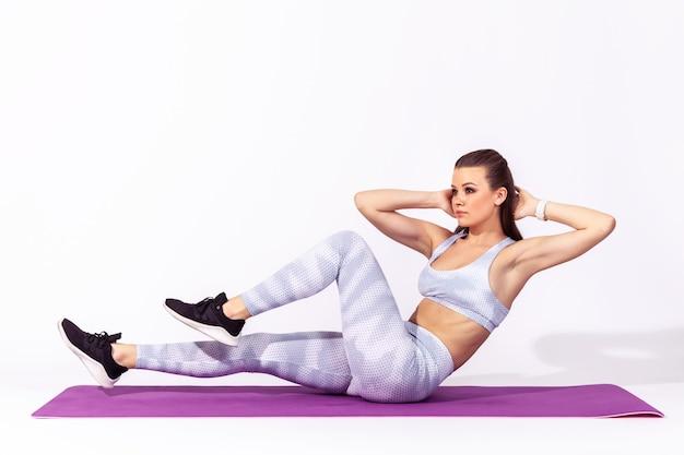 Vrouw doet abdominale crunches-oefeningen op yogamat, pompende buikspieren, lichaamsverzorging