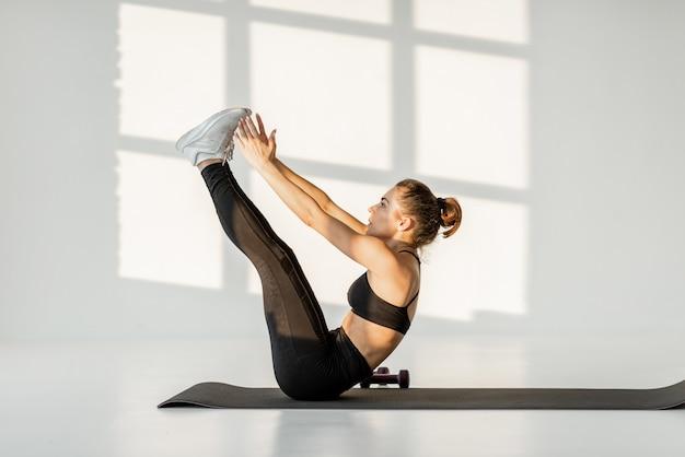 Vrouw doet alleen fitness in de witte kamer