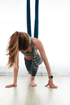 Vrouw doet anti-zwaartekracht aero-yoga in een kamer met luchthangmatten, warmt zich op en strekt zich uit voordat ze in luchthangmatten traint.