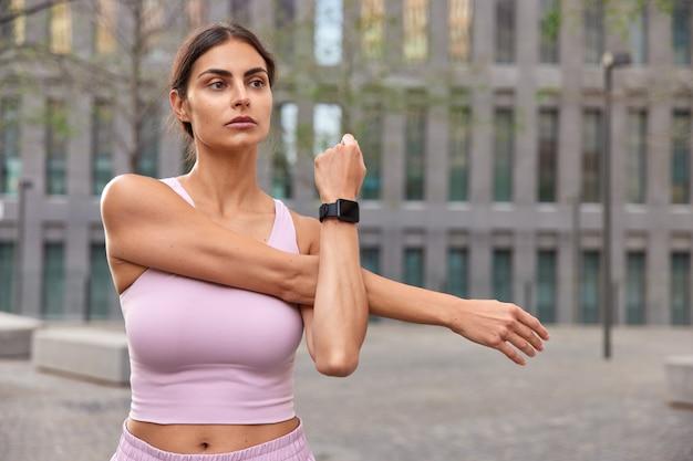 Vrouw doet arm strekken heeft bepaald expressie warmt op voordat de training smartwatch draagt cropped top poseert in de buurt van modern gebouw gericht op afstand
