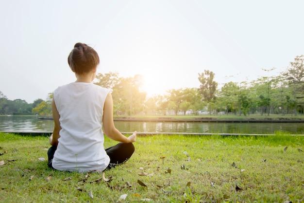 Vrouw doet bemiddeling en yoga op groen ingediend Premium Foto